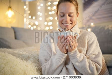Cosy woman in 30s at home with hot chocolate