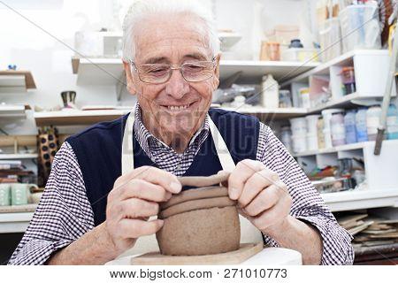 Senior Man Making Coil Pot In Pottery Studio