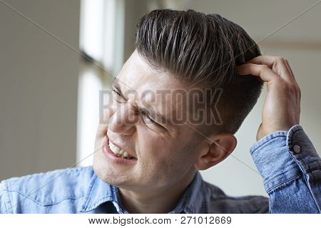 Shot Of Young Man Indoors Itching Scalp