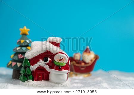 Happy Santa Claus With Gifts Box On The Snow Sled Going To Snow House. Near Snow House Have Snowman