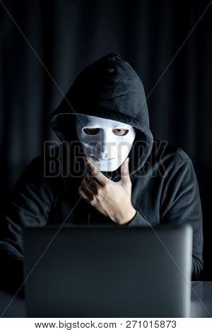 Mystery Male Hoodie Hacker Holding White Mask Looking At Laptop Computer. Anonymous Social Masking.
