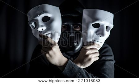 Mystery Hoody Man Wearing Black Mask Holding Two White Masks In His Hand. Anonymous Social Masking.