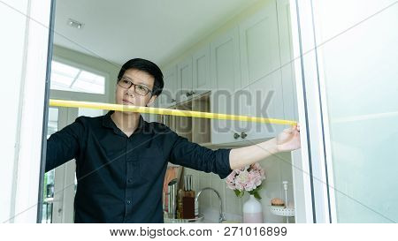 Young Asian Worker Man Using Tape Measure On Door Frame In The Kitchen. Home Interior Designer Measu