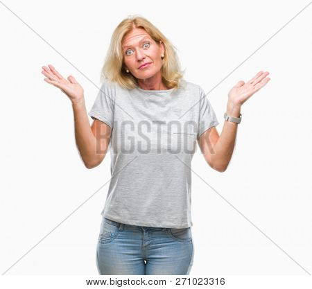 Middle age blonde woman over isolated background clueless and confused expression with arms and hands raised. Doubt concept.