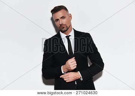 Confident In His Style. Handsome Young Man In Full Suit Adjusting Sleeve And Looking At Camera While