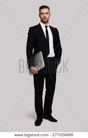 Pure Confidence. Full Length Of Handsome Young Man In Full Suit Carrying Laptop And Looking At Camer
