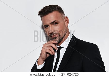 Young And Confident. Handsome Young Man In Full Suit Keeping Hand On Chin And Looking At Camera With