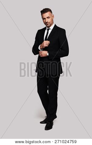 Confident And Handsome. Full Length Of Handsome Young Man In Full Suit Adjusting Sleeve And Smiling