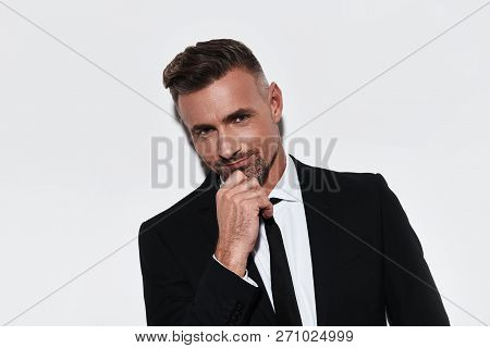 Confident Business Expert. Handsome Young Man In Full Suit Keeping Hand On Chin And Looking At Camer