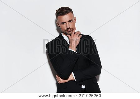 Portrait Of Confidence. Handsome Young Man In Full Suit Keeping Hand On Chin And Looking At Camera W