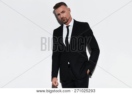 Confident Manager. Handsome Young Man In Full Suit Keeping Hand In Pocket And Looking At Camera Whil