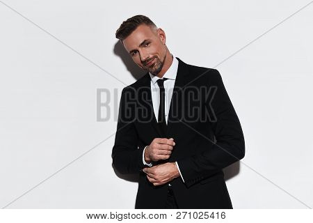 Portrait Of Confidence. Handsome Young Man In Full Suit Adjusting Sleeve And Looking At Camera With