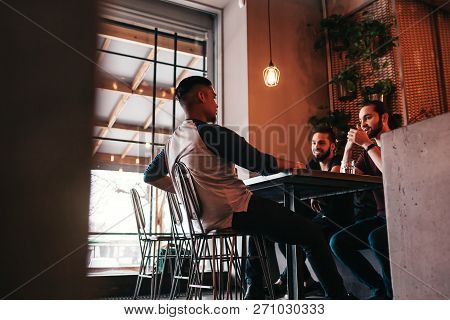 Group Of Mixed Race Young Men Talking In Lounge Bar. Multiracial Friends Having Fun In Cafe