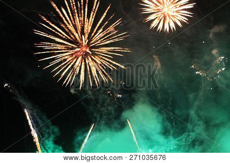 Fireworks. Firework. Heavenly Background. A Colorful Wave Of Bright Green And Orange Shimmering Ligh