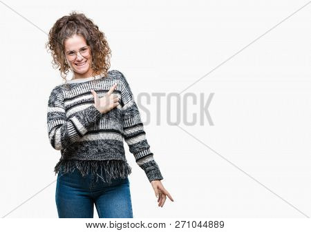 Beautiful brunette curly hair young girl wearing glasses over isolated background cheerful with a smile of face pointing with hand and finger up to the side with happy and natural expression on face