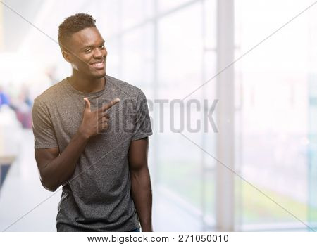 Young african american man wearing grey t-shirt cheerful with a smile of face pointing with hand and finger up to the side with happy and natural expression on face looking at the camera.