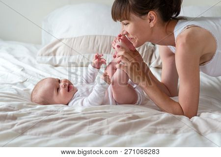 Mother And Her Cute Baby Laughing And Playing On The White Bed