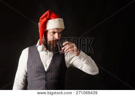 Santa Man Drinking Glass Of Whiskey. Serious Man In Santa Hat Drinking Whiskey. Man In Waistcoat Tas