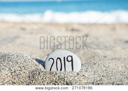 closeup of a stone, with the text number 2019, as the new year, handwritten in it, on the sand of a lonely beach, with the ocean in the background