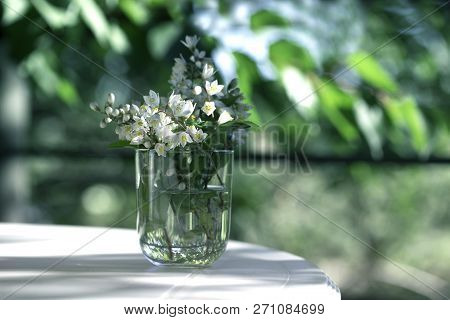 Flower Bouquet In Glass Vase On A White Table In Green Garden. Spring Or Summer Flower In A Glass Ja
