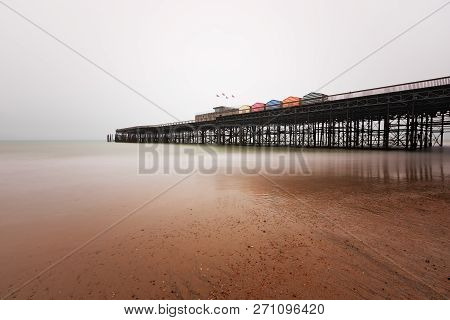 Hastings Pier In Winter With An Overcast Sky And Slow Shutter Speed
