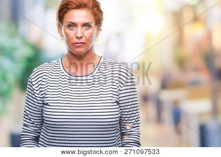 Atrractive senior caucasian redhead woman over isolated background with serious expression on face. Simple and natural looking at the camera.