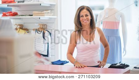 Beautiful middle age hispanic woman standing with smile on face at clothes store. Shop owner and shop assistant smiling confident and cheerful at desk.