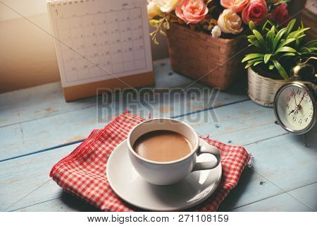 Cup Of Coffee With Desktop Calendar 2019,clock And Pot Of Rose Flower On Blue Wooden Desk.calendar F