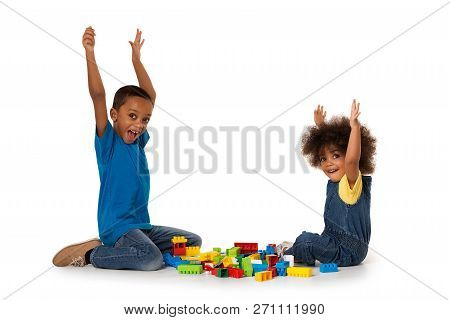 Two Little Cute African American Children Playing On The Floor With Lots Of Colorful Plastic Blocks