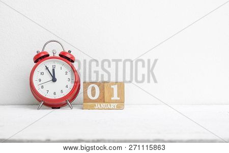 Close Up Of Wooden Calendar Date 01 January With Red Alarm Clock On White Grunge Wood Table With Cop