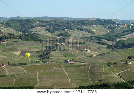 Piemonte, Italy 04-10-2011 Yellow Hot Air Balloon Rises Over The Vineyards Of Northern Italys Piemon