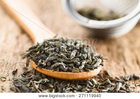 Dried Green Tea Leaves On Wooden Spoon, Photographed On Wood (selective Focus, Focus One Third Into