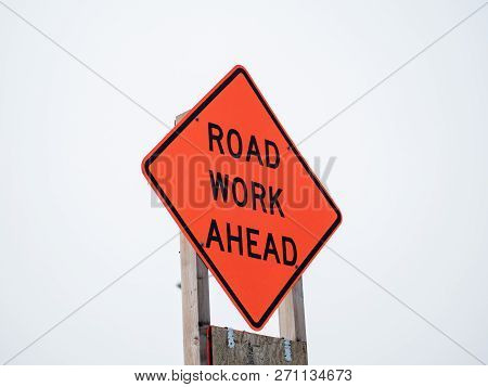 Road Work Ahead Orange Sign Posted On Wooden Post With Overcast Sky