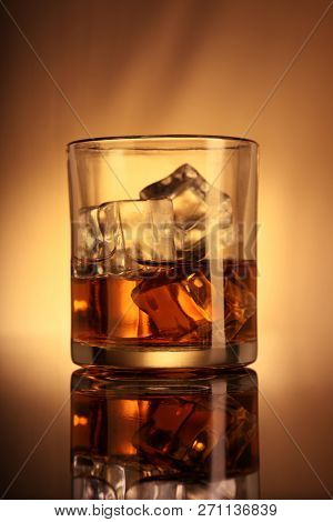 Single Whiskey Glass With Ice Cubes On Amber Background