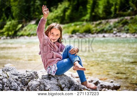 Little Girl Sitting On River Rock After Nature Hiking.