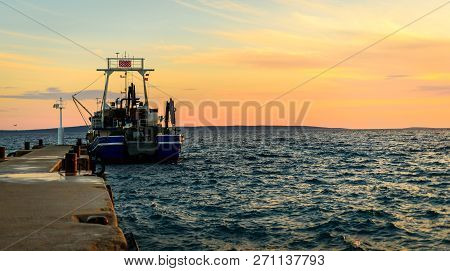 Fishing Boat Moored Or Docked At Pier In Sunset.