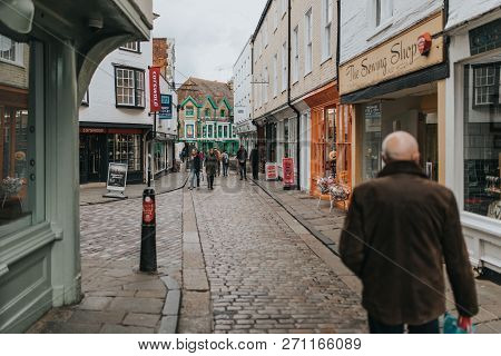Canterbury, England - October 28th, 2018: Pedestrian Walking Along Cobblestoned Street, With Shops A