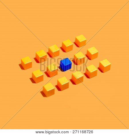 Rows Of Yellow Cubes On Yellow Background And Among Them Blue. Minimal Style. Symbolic Concept Of Co