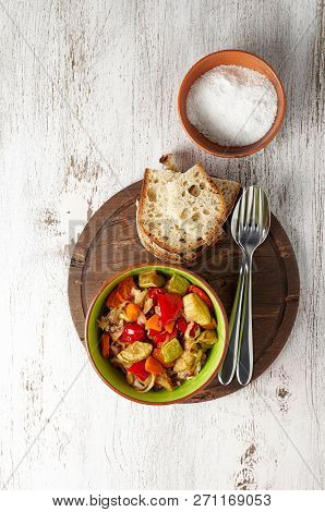 Vegan cabbage, carrot, paprika and zucchini stew. Portion of sauteed vegetables with artisan bread on vintage wooden table. Close up view poster