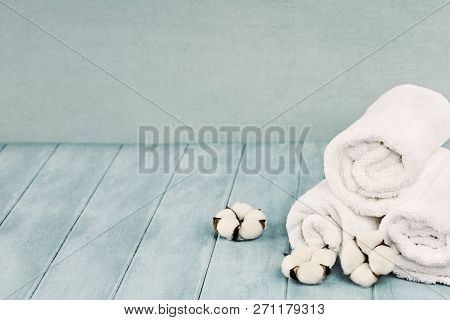 Rolled Up White Fluffy Towels With Cotton Flowers Against A Blurred Blue Background With Free Space