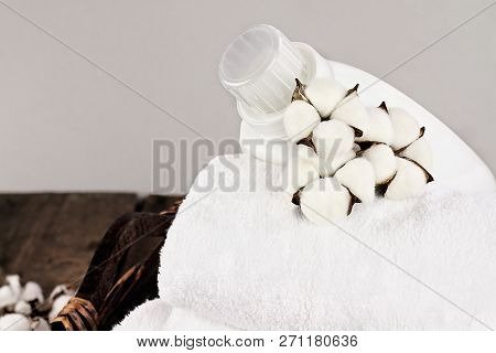 Laundry Basket Filled White Fluffy Towels, Cotton Flowers And A Bottle Of Liquid Soap Against A Blur