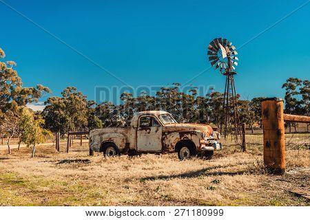 Kapunda, South Australia - June 17, 2017: Rusty Holden Fj Ute And Vintage Kookaroo Windmill On Displ