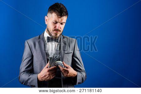 Man Formal Suit Hold Pile Of Dollar Banknotes Blue Background. Businessman Got Cash Money. Richness