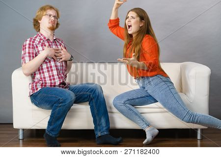 Man And Woman Having Horrible Fight While Sitting On Sofa. Friendship, Couple Breakup Difficulties A