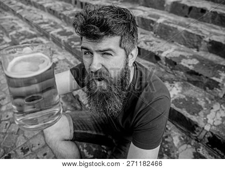 Guy having rest with cold draught beer. Hipster on cheerful face drinking beer outdoor, raising drink up. Man with beard and mustache holds glass with beer while sits on stone stairs. Cheers concept poster