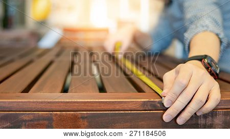 Young Asian Man Using Tape Measure For Measuring Wooden Outdoor Table In Showroom. Shopping Furnitur