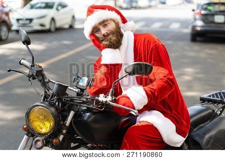 Dull Christmas Biker Feeling Bored. Bearded Young Man In Santa Costume Sitting On Parked Motorcycle,