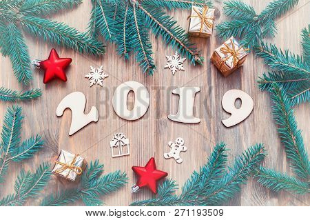 New Year 2019 background -2019 figures, Christmas toys, blue fir tree branches and snowflakes. New Year 2019 festive seasonal still life