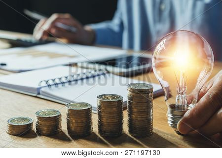 Business Man Holding Light Bulb On Desk In Office And Putting Calculator With Coins Or Money On Work