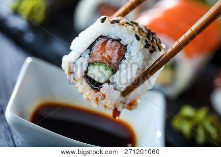 Sushi Set Sashimi And Sushi Rolls Served On Stone Slate.